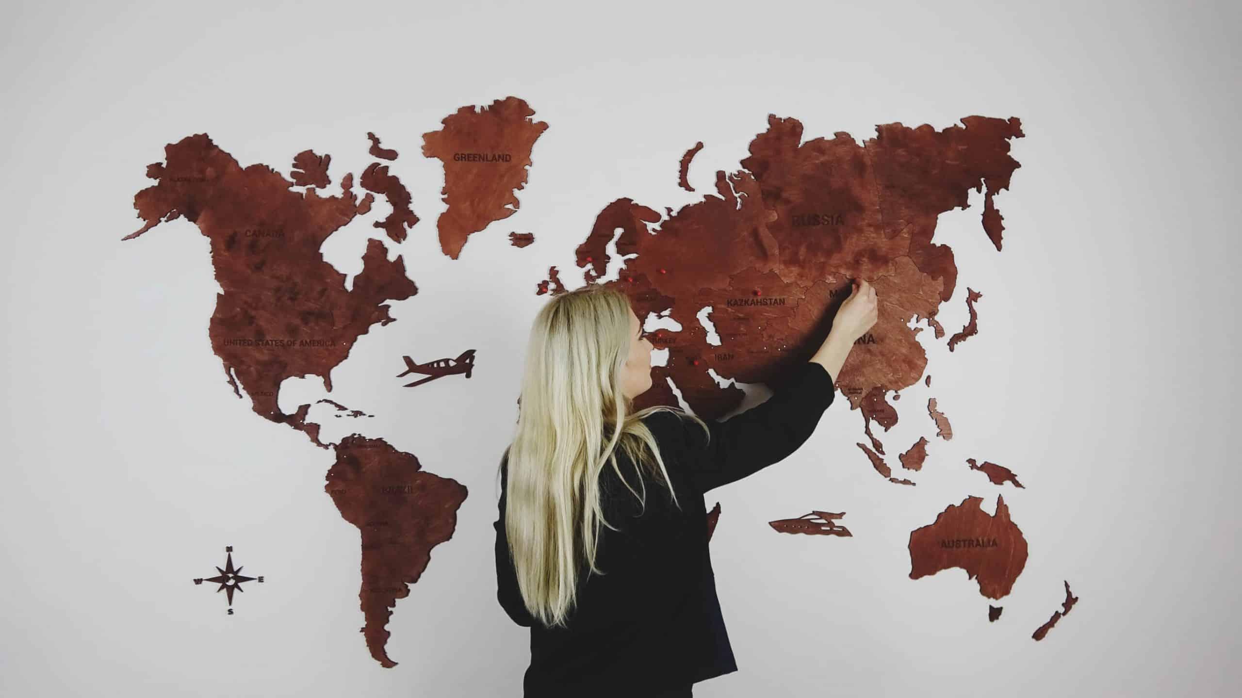 Medinis pasaulio žemėlapis kabinamas ant sienos su smeigtukais. Darbo pavyzdys
